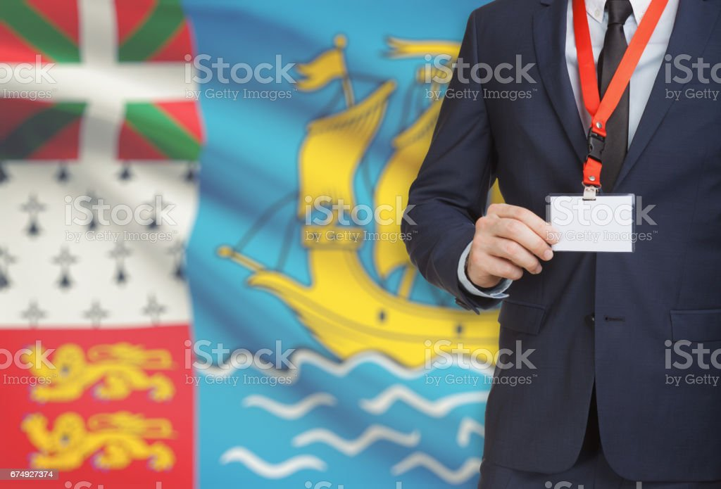 Businessman holding name card badge on a lanyard with a national flag on background - Saint Pierre and Miquelon royalty-free stock photo