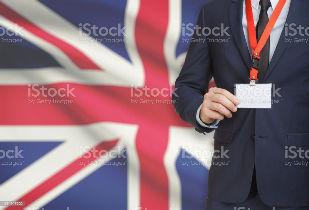 Businessman holding name card badge on a lanyard with a national flag on background - United Kingdom royalty-free stock photo