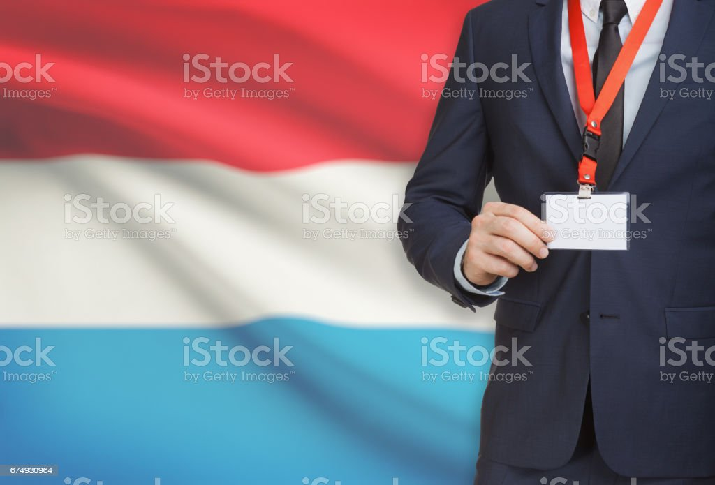 Businessman holding name card badge on a lanyard with a national flag on background - Luxembourg royalty-free stock photo