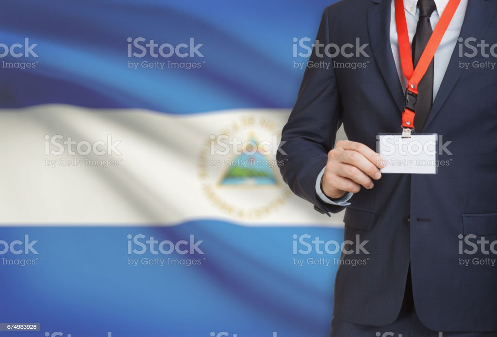 Businessman holding name card badge on a lanyard with a national flag on background - Nicaragua - foto de stock