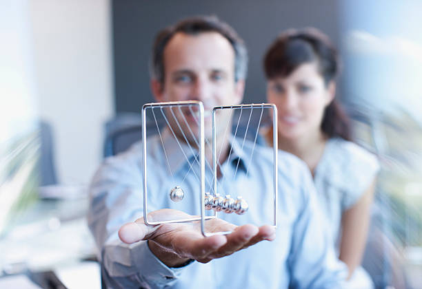 businessman holding newtons cradle in office - perpetual motion stock photos and pictures