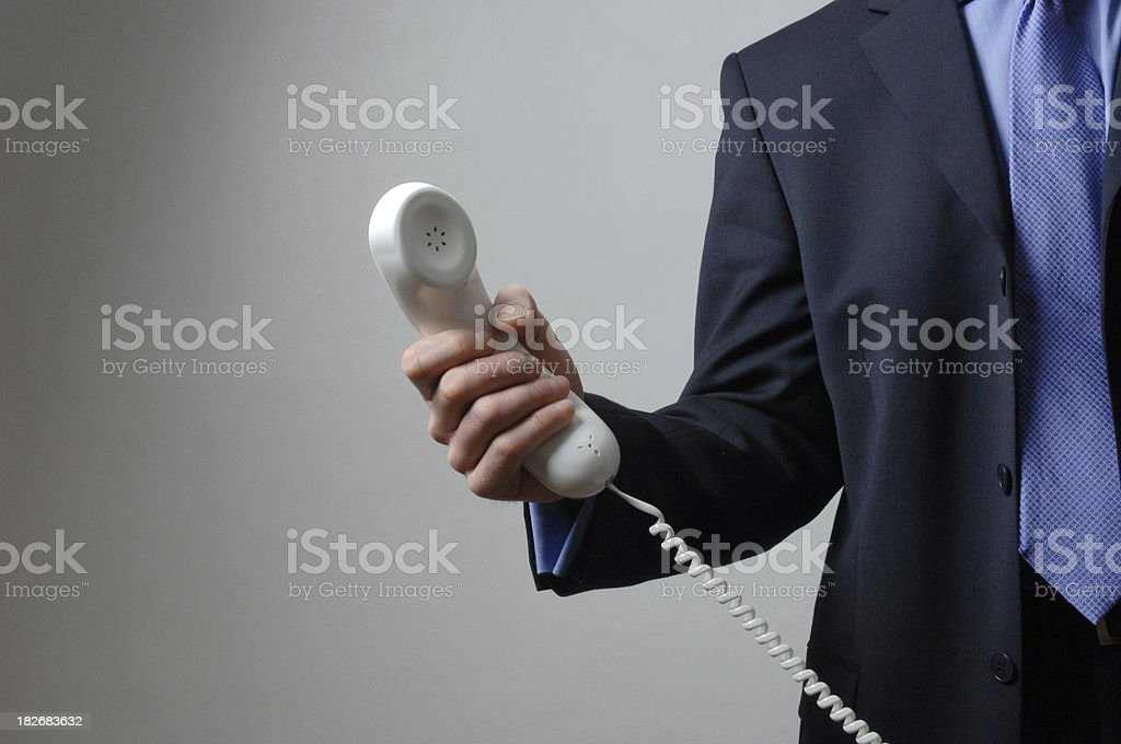 Businessman holding out phone royalty-free stock photo