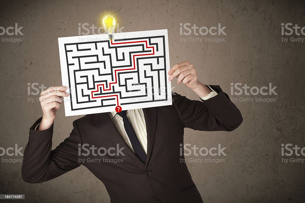 Businessman holding paper with a labyrinth on it in front royalty-free stock photo