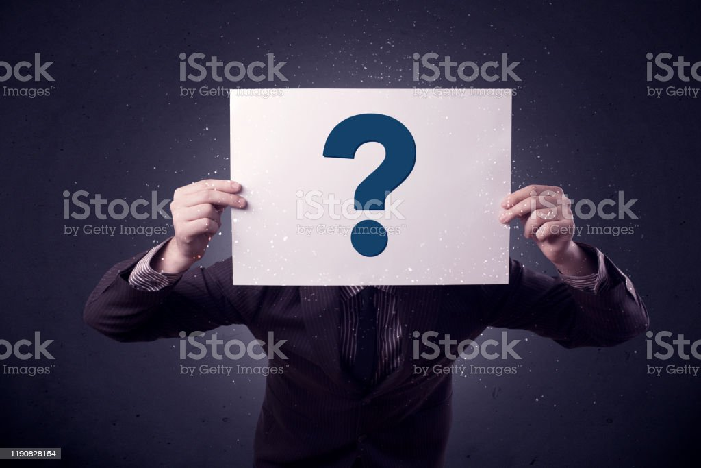 Businessman holding paper with question marks Young businessman hiding behind a question mark drawn on paper Achievement Stock Photo