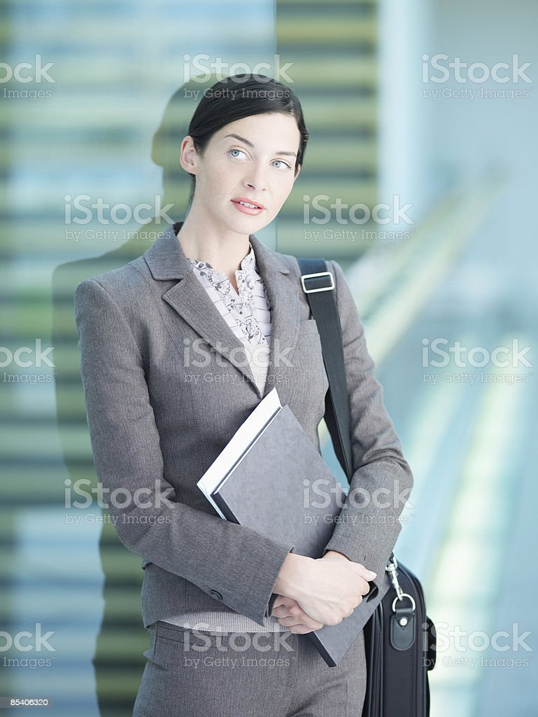 Businessman holding paperwork and briefcase royalty-free stock photo