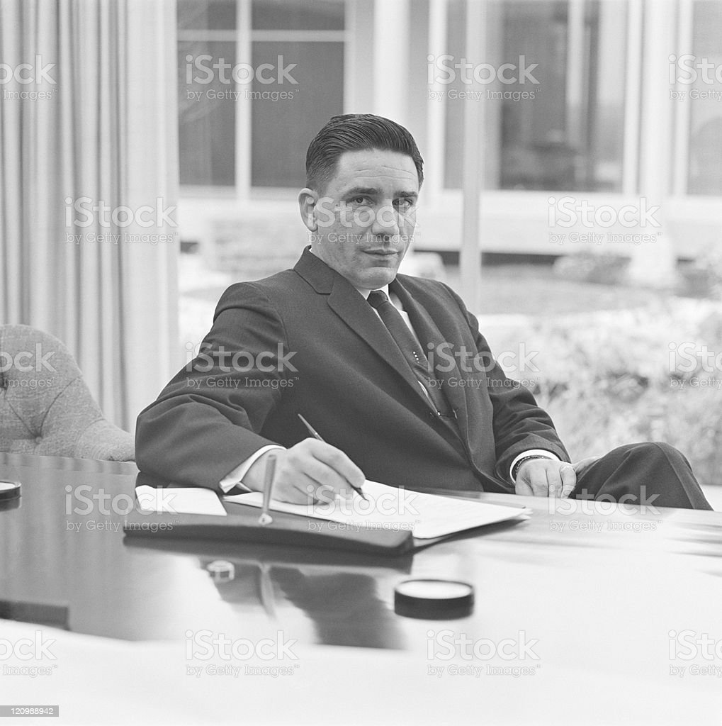 Businessman holding pen, portrait stock photo