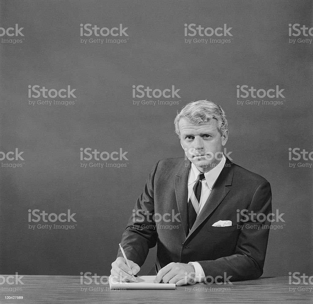 Businessman holding pencil and notepad, portrait stock photo