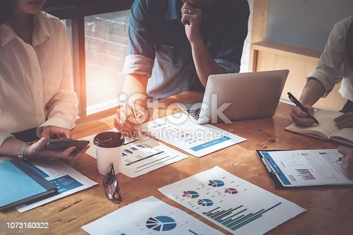 istock Businessman holding pens and holding graph paper are meeting to plan sales to meet targets set in next year. audit budget and financial concept 1073160322