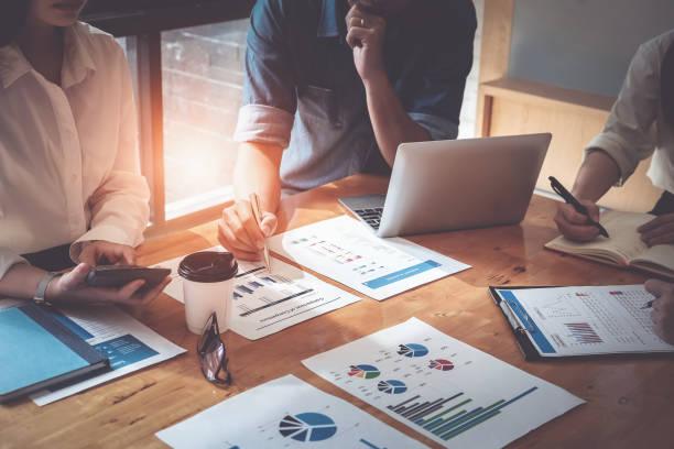 homme d'affaires détenant des stylos et tenir le papier millimétré se réunissent pour planifier les ventes pour répondre aux objectifs fixés dans l'année prochaine. audit budgétaire et financier concept - graph photos et images de collection