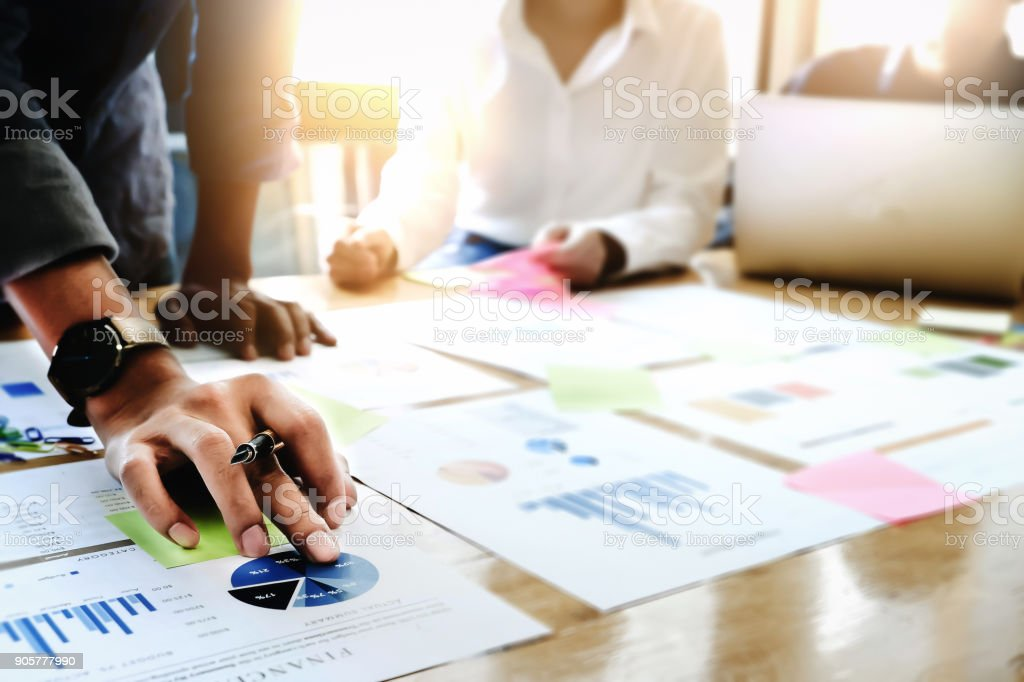 Businessman holding pens and holding graph paper are meeting to plan sales to meet targets set in next year. stock photo