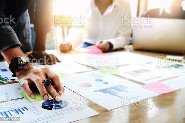 Businessman holding pens and holding graph paper are meeting to plan sales to meet targets set in next year.
