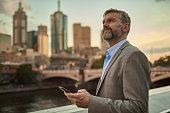 Businessman holding phone at dusk in Melbourne centre city.