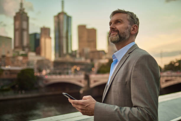 Businessman holding phone at dusk in Melbourne centre city stock photo