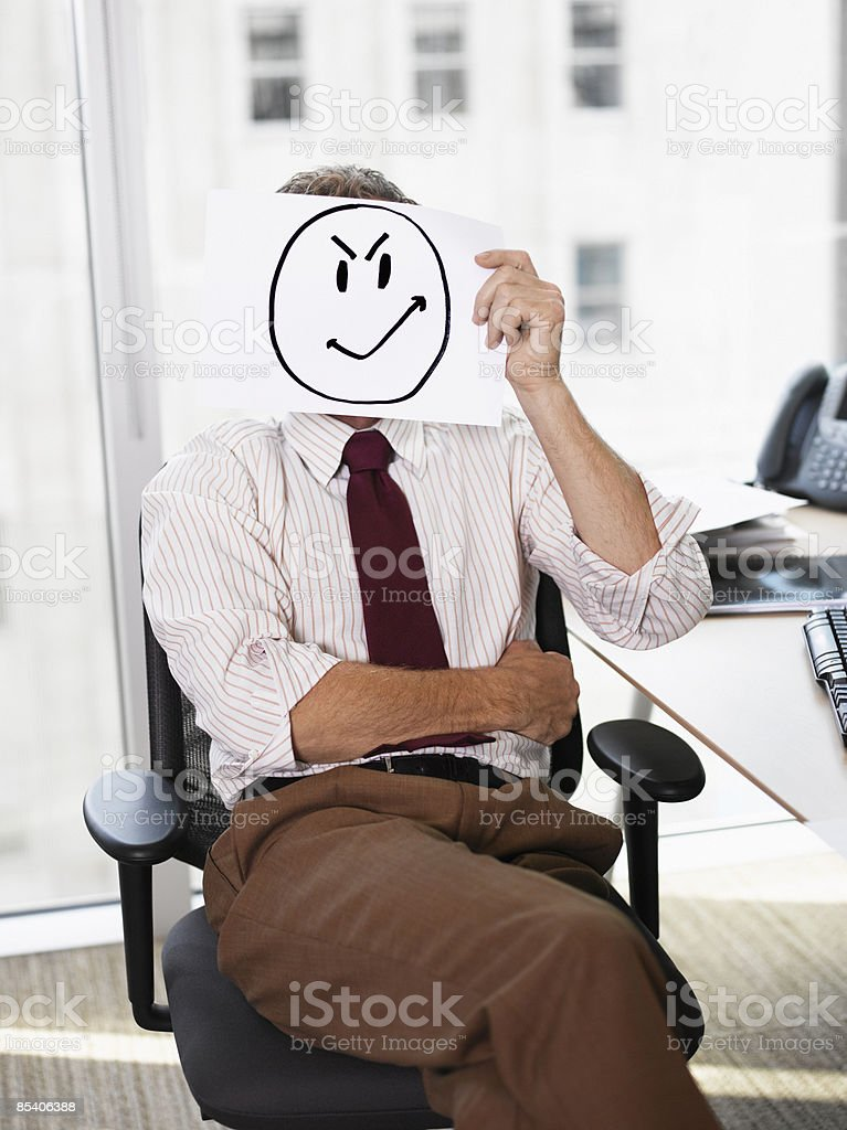Businessman holding picture of angry face royalty-free stock photo
