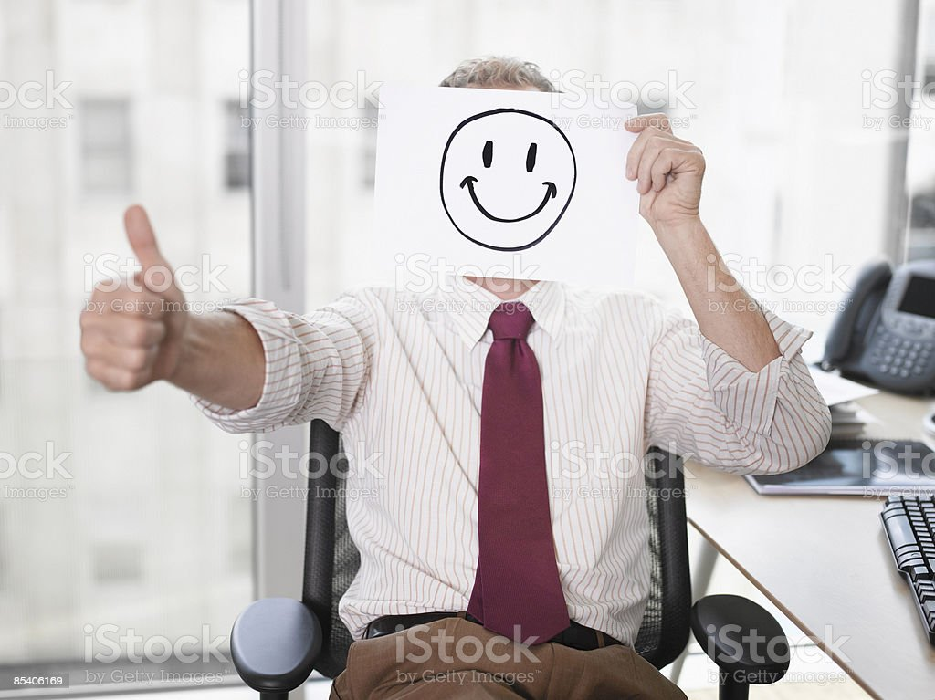 Businessman holding picture of happy face stock photo