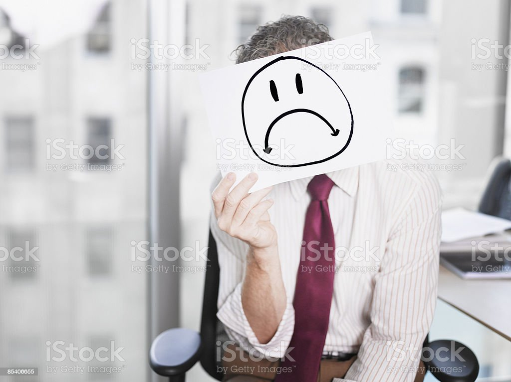 Businessman holding picture of sad face royalty-free stock photo