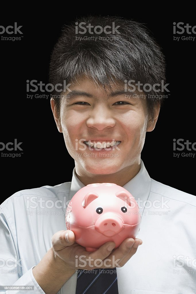 Businessman holding piggy bank, smiling, portrait royalty-free 스톡 사진
