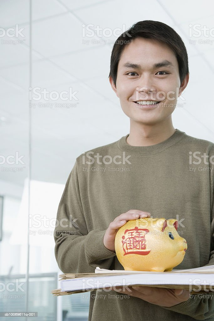 Businessman holding piggybank with file, smiling, portrait royalty-free stock photo