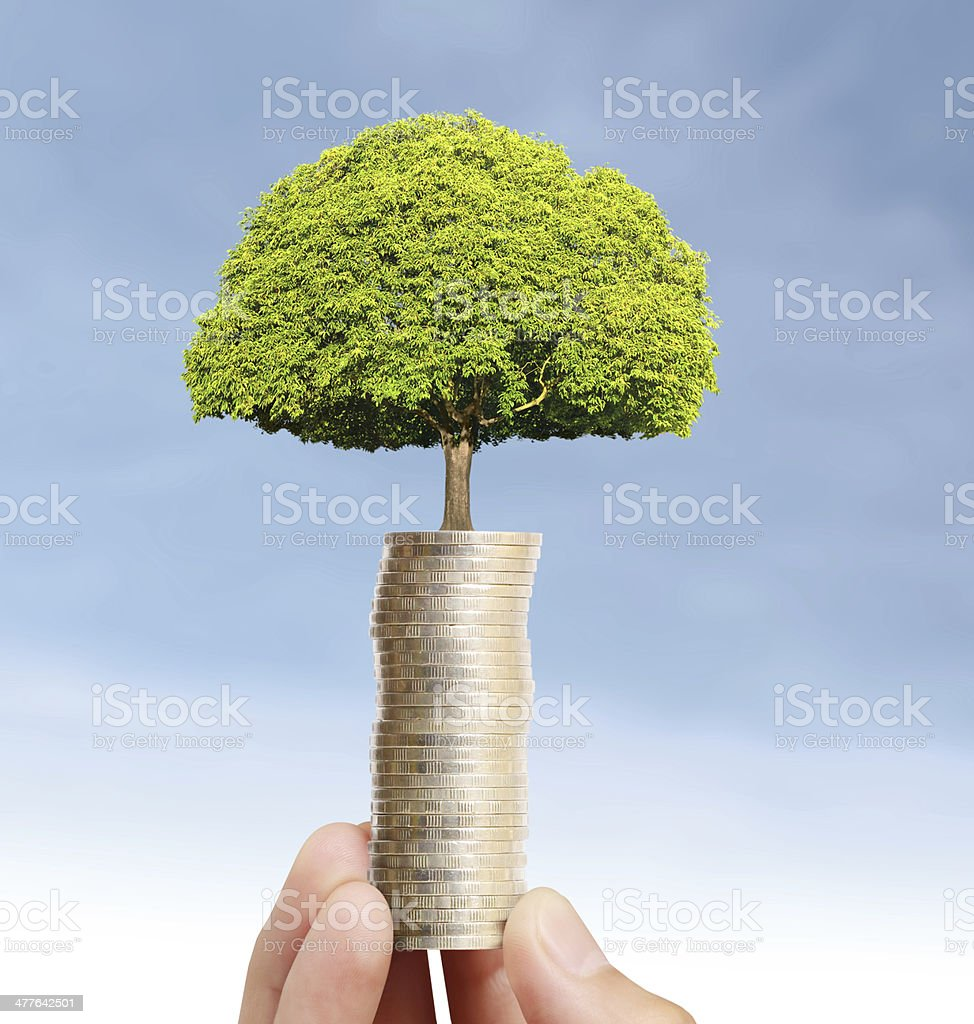 Businessman holding plant sprouting from  handful of coins royalty-free stock photo