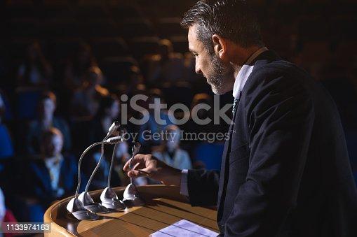 1133856033 istock photo Businessman holding podium speaker in his hand at auditorium 1133974163