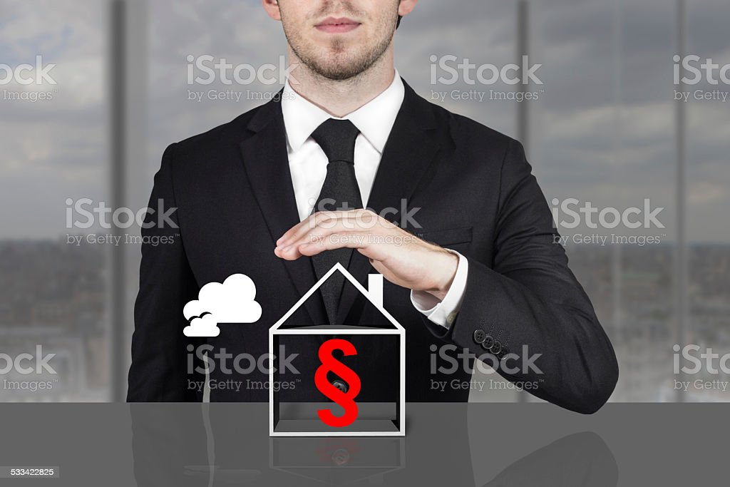 businessman holding protective hand above building paragraph sym stock photo