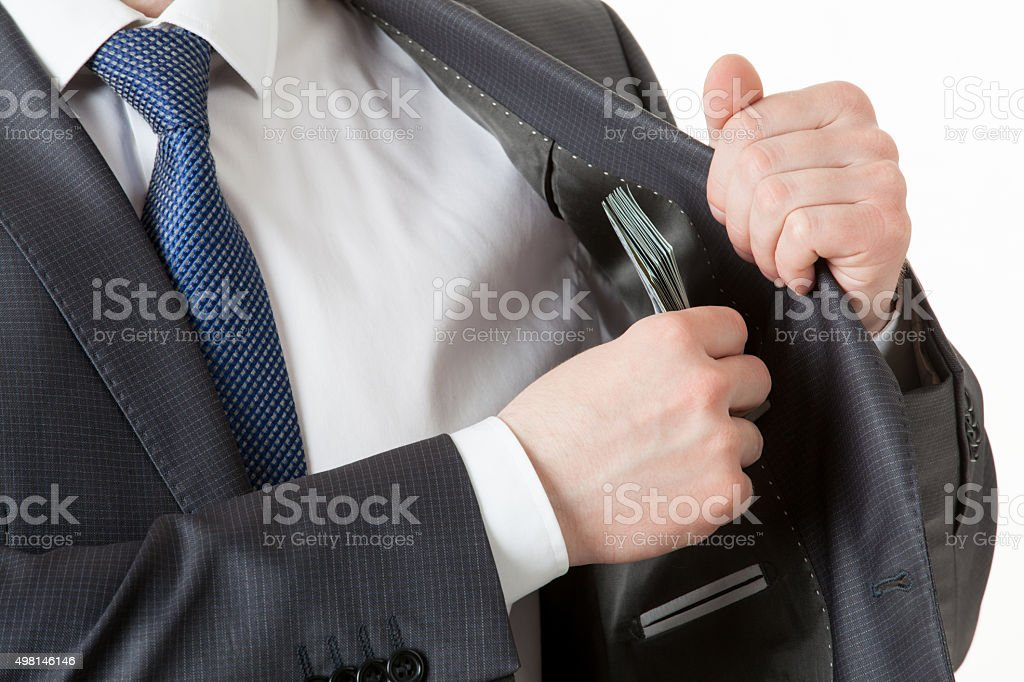 Businessman holding putting dollars in a pocket stock photo