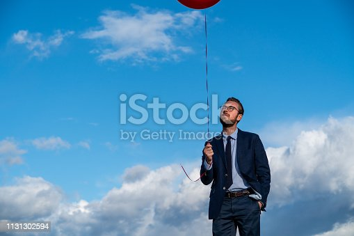 Young businessman in a suit standing on top of a hill with a red balloon against a blue sky with white clouds.