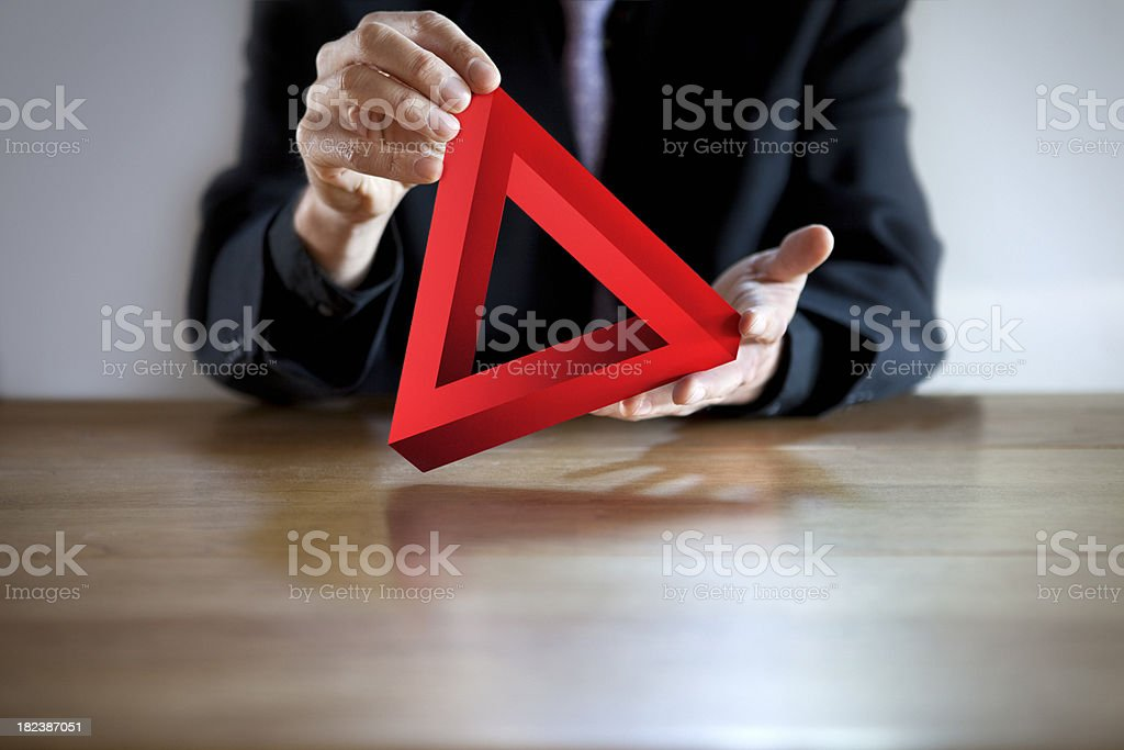 Businessman Holding Red Impossible Triangle Puzzle royalty-free stock photo