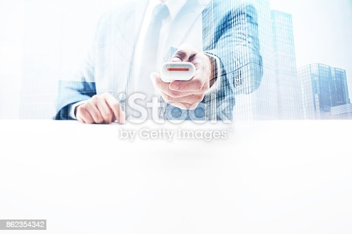 Businessman sitting by the desk holding remote control with double exposure cityscape.