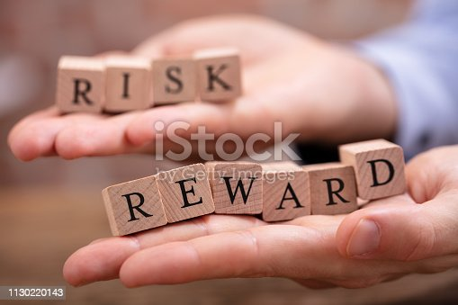 Close-up Businessman's Hand Holding Risk And Rewards Blocks Over Wooden Table