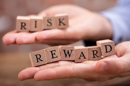 istock Businessman Holding Risk And Rewards Blocks 1130220143