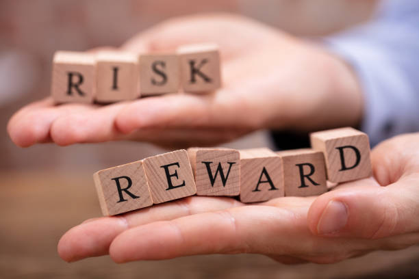 businessman holding risk and rewards blocks - rischio foto e immagini stock
