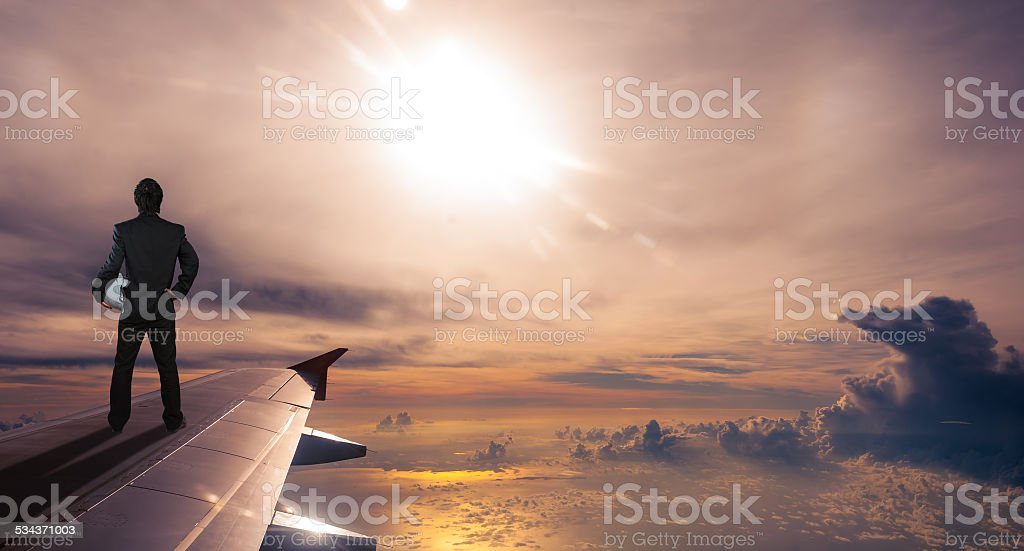 businessman holding safety helmet standing on airplane wing stock photo