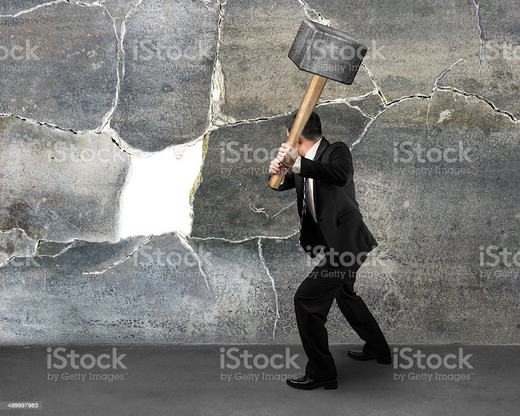 Businessman holding sedgehammer to crack wall stock photo