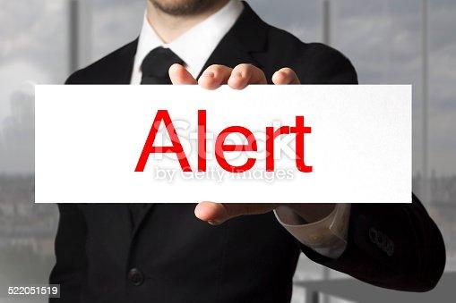 businessman in black suit holding sign alert