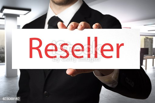businessman in office holding sign reseller