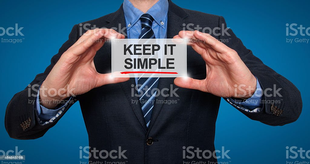Businessman holding sign that says KEEP IT SIMPLE stock photo