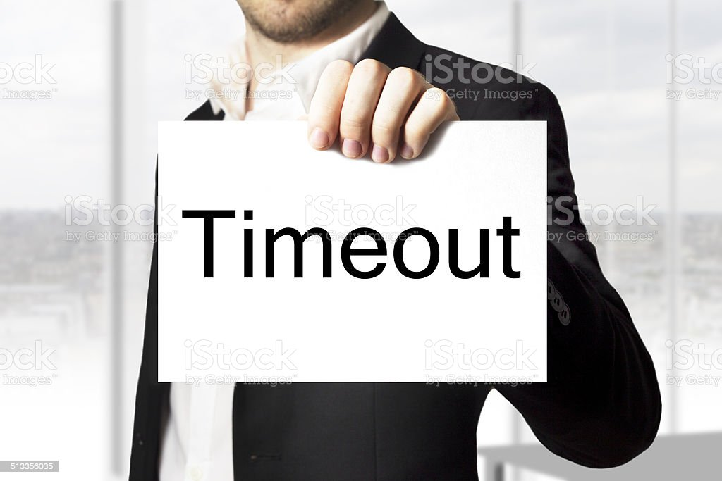 businessman holding sign timeout stock photo