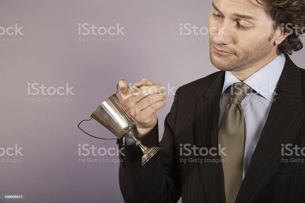 Businessman Holding Small Trophy stock photo