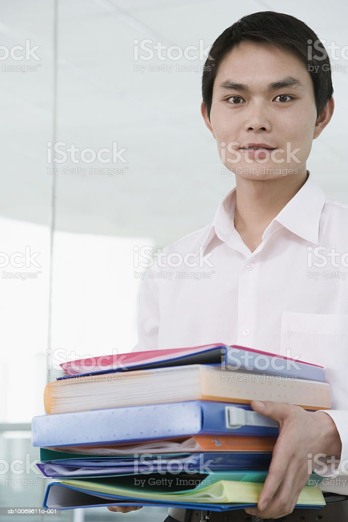 Businessman holding stack of files, smiling, portrait royalty-free stock photo