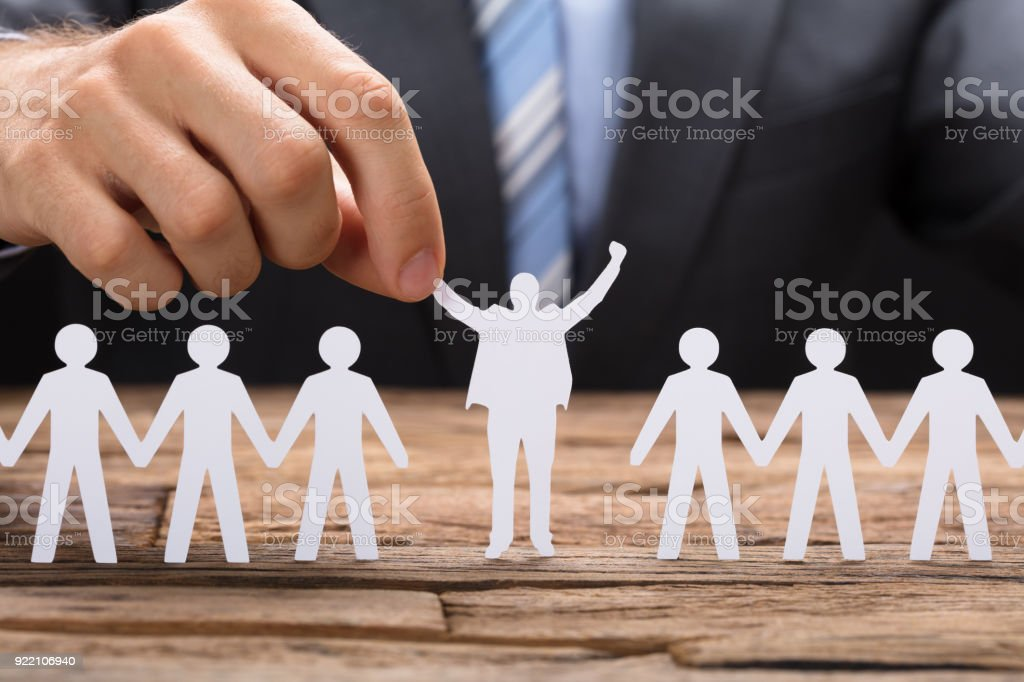 Businessman Holding Successful Paper Executive Amidst Teamchain stock photo