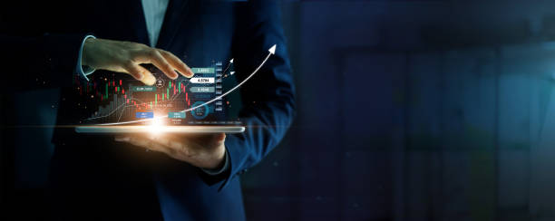 Businessman holding tablet and analysis stock market, currency exchange and banking, showing a growing virtual hologram of statistics, graph and chart, Business growth, planing and strategy  concept. stock photo