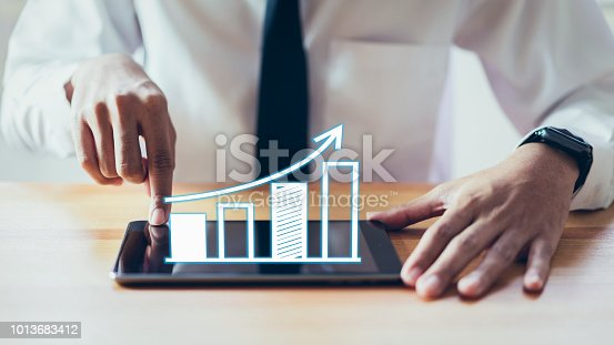1051659174 istock photo Businessman holding tablet and have a chart showing business growth. positive indication of income. 1013683412