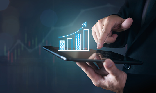 istock Businessman holding tablet and have a chart showing business growth. positive indication of income. 990347180