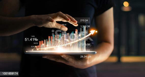 istock Businessman holding tablet and showing a growing virtual hologram of statistics, graph and chart with arrow up on dark background. Stock market. Business growth, planing and strategy concept. 1051659174