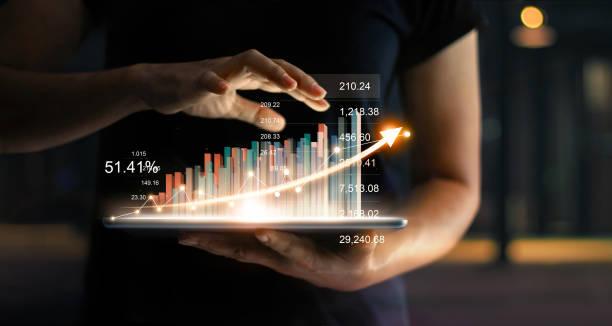 geschäftsmann tablet halten und eine wachsende virtuelle hologramm statistiken, diagramm und tabelle mit pfeil auf dunklem hintergrund auftauchen. aktienmarkt. business-strategie für wachstum, planung und konzept. - geschäftsstrategie stock-fotos und bilder
