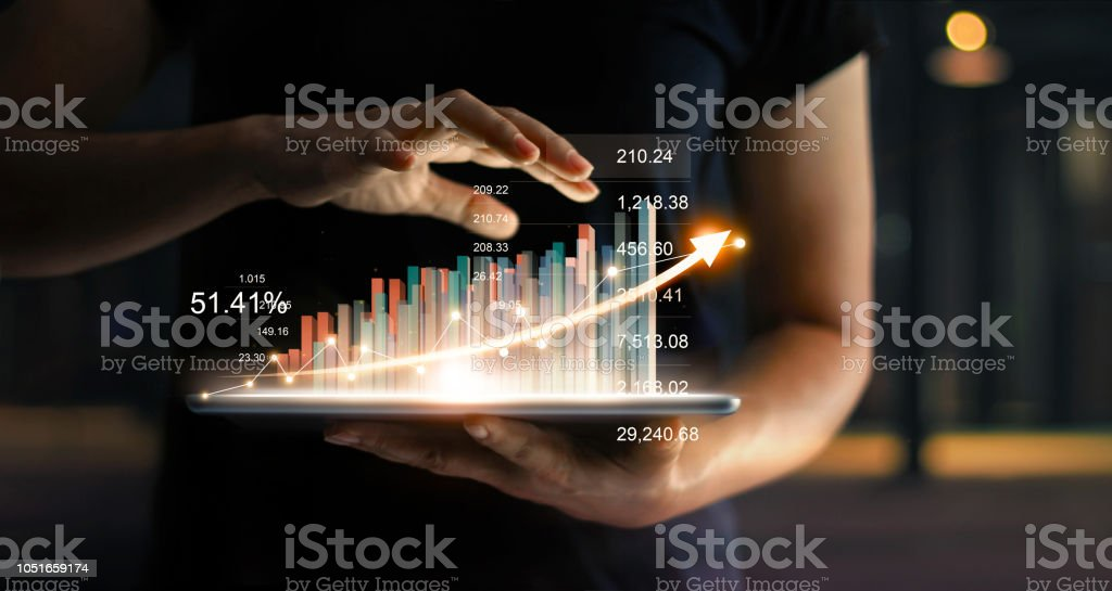 Businessman holding tablet and showing a growing virtual hologram of statistics, graph and chart with arrow up on dark background. Stock market. Business growth, planing and strategy concept. stock photo