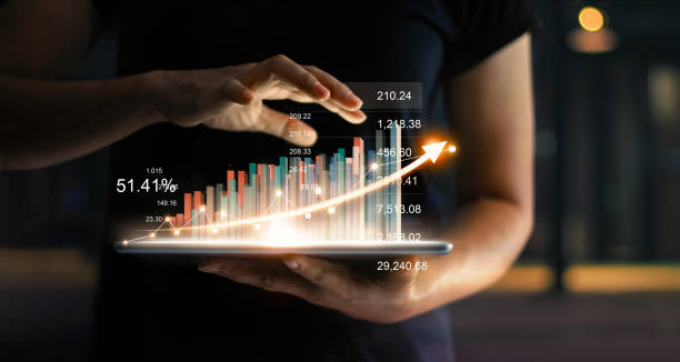 businessman holding tablet and showing a growing virtual hologram of statistics, graph and chart with arrow up on dark background. stock market. business growth, planing and strategy concept. - hologram stock photos and pictures