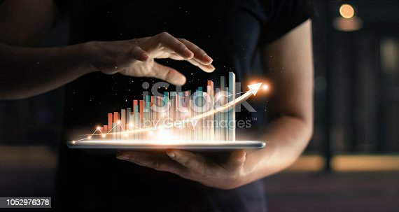 1051659174istockphoto Businessman holding tablet and showing a growing virtual hologram of statistics, graph and chart with arrow up on dark background. Stock market. Business growth, planing and strategy concept. 1052976378