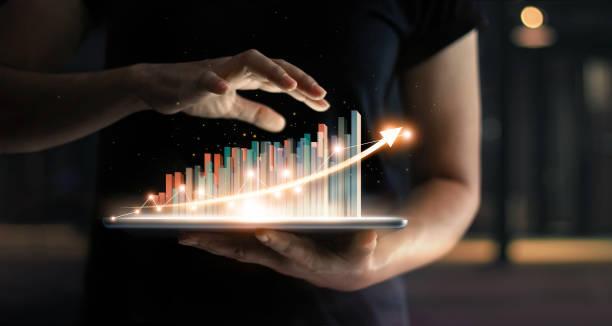 homme d'affaires détenant tablet et montrant un hologramme virtuel grandissant de statistique, graphique et tableau avec flèche sur fond sombre. marchés boursiers. concept croissance, rabotage et stratégie d'entreprise. - graph photos et images de collection